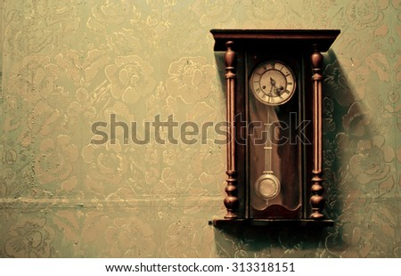 Antique clock on the wall with textured wallpaper - stock photo