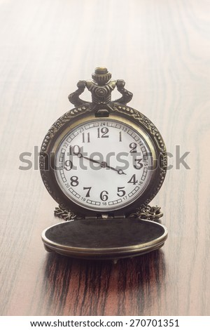 Antique clock vintage on wood background. - stock photo