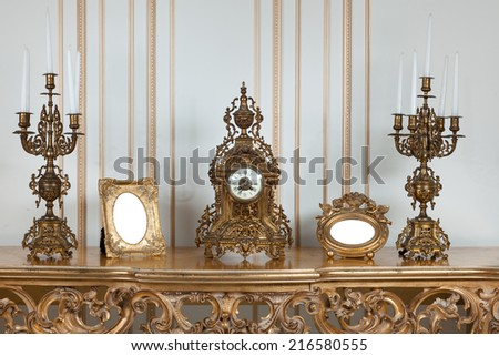 Antique clock with candlesticks stand on antique table. - stock photo