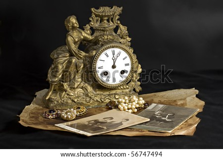 Antique clocks, jewelry and photographs on a dark background - stock photo
