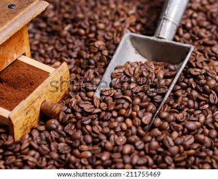 Antique coffee grinder with grinded coffee in scoop on beans - stock photo