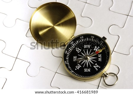 Antique compass on jigsaw puzzle pieces - stock photo