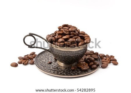 Antique cup full of coffee beans, isolated on white.