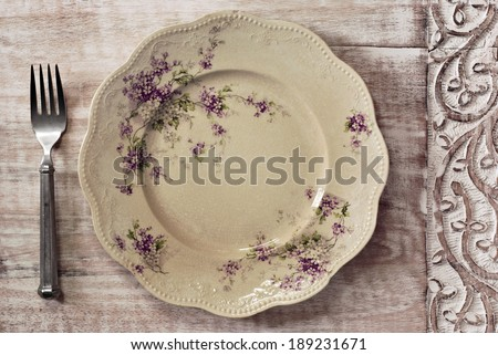 Antique decorative dinner plate (with authentic surface crazing) and vintage pewter fork on distressed wood with decorative carved border.  - stock photo