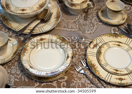 Antique dinner place setting on table - stock photo