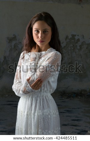 Antique edwardian lace dress worn by a beautiful woman against an old wall