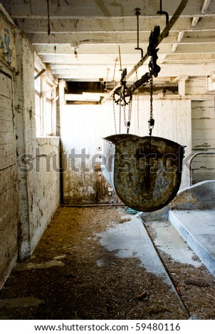 Antique empty cow stable covered in cobwebs and hay glowing with warm light. - stock photo