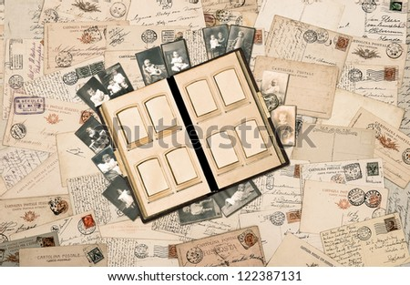 antique family album over nostalgic vintage background with old handwritten postcards, photos, pictures