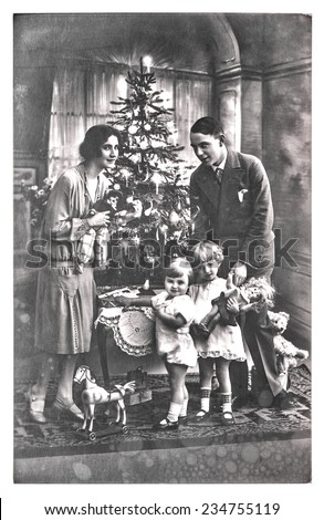 antique family portrait of parents and children with christmas tree. vintage picture with original film grain and blur. black and white photo - stock photo