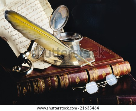 Antique feather pen with old books, glasses and manuscript - stock photo
