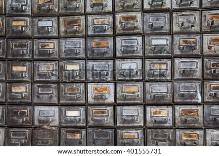 Antique filing system. Retro design metal boxes with aged paper nameplates. Old time storage cabinet. Information management and security concept image. Textured, shabby, dirty silver surface - stock photo