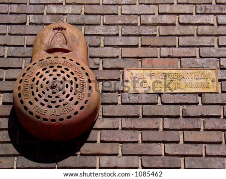 Antique fire alarm gong with sign on old brick wall - stock photo