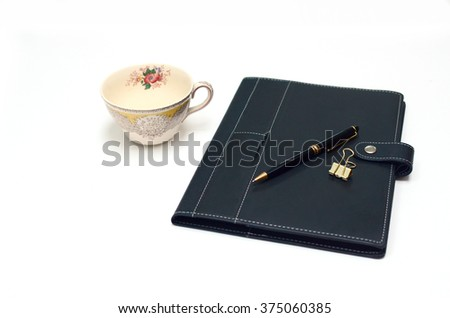 Antique flower tea cup with notebook and pen, side view