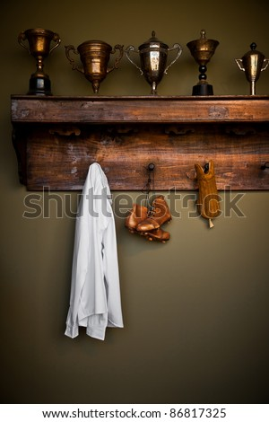 Antique football equipment and trophies in a vintage locker room - stock photo