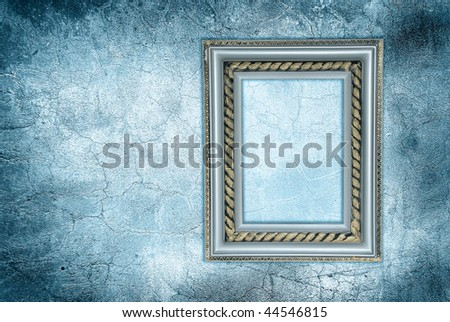 antique frame on a frozen grunge wall - stock photo