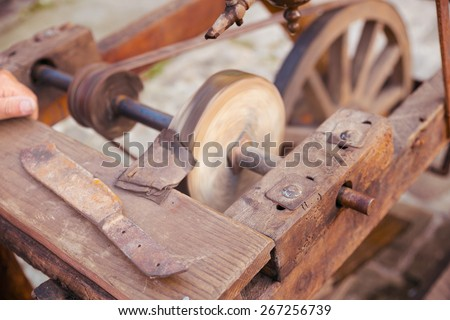 Antique frame with grinding wheel for sharpening knives in medieval times - stock photo
