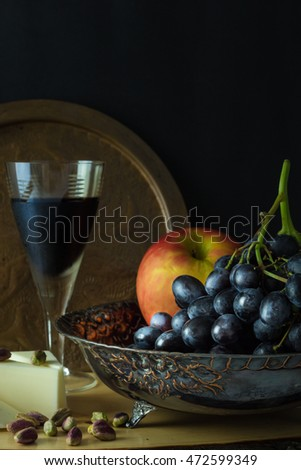 Antique fruit bowl with cluster of grapes, apple with pieces vegan cheese, pistachios and a glass of red wine