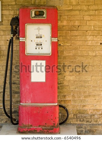 Antique gas pump with white sticker against grungy brick wall