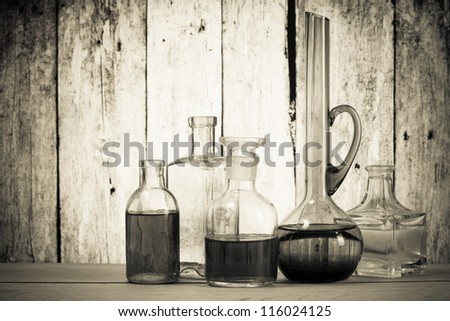 Antique glass bottles and in front of old wooden background