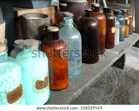 Antique glass bottles holding various chemicals, sitting on laboratory shelf.