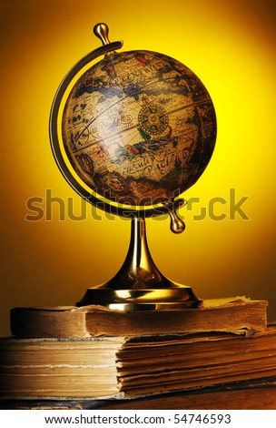 Antique globe on old books over yellow - stock photo