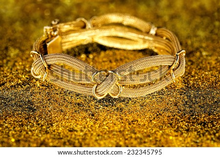 antique gold bracelet on sparkling surface - stock photo