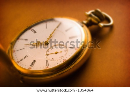 Antique gold pocket watch on brown leather background