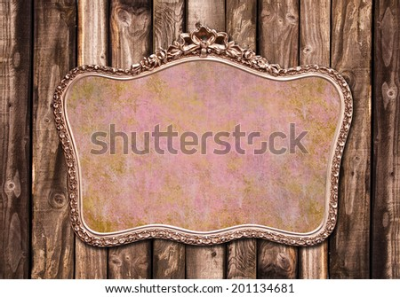 Antique golden frame hanging on a wooden wall - stock photo