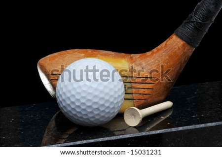 Antique Golf Club with Ball and Tee on Black Background