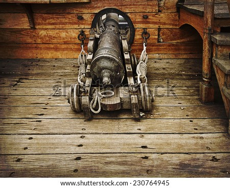 Antique gun ready to fire on antique vessel on grunge texture - stock photo