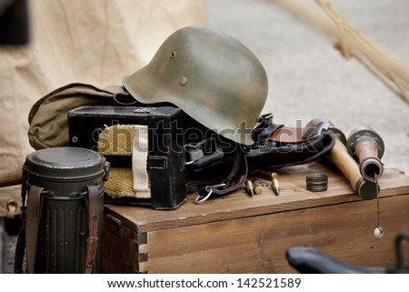 Antique helmet and other military  equipment over a wooden box.  Military equipment.