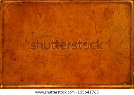 Antique, honey-coloured, leather-bound book cover with gilded banding and tooling . Textured, distressed and marked from ages of use. Grunge background. - stock photo