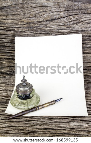 antique  ink pen  and glass inkwell, old paper on wooden background - stock photo