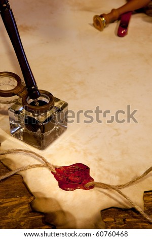 Antique ink pot on a parchment scroll with wax seal - stock photo