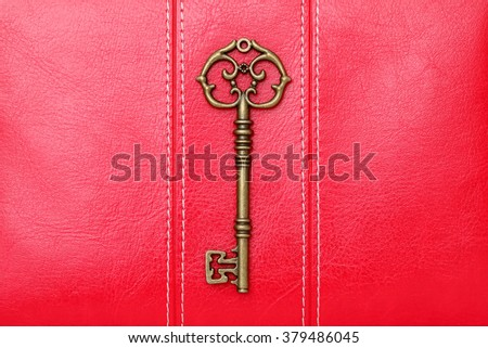 Antique key on red leather background  - stock photo