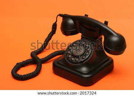 Antique landline phone on orange backdrop