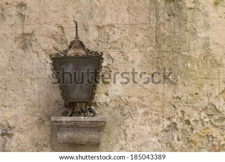 Antique lantern against the aged painted wall - stock photo