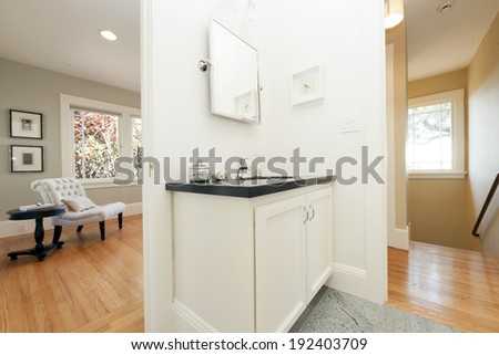 Antique luxury Bathroom in white with sink with black granite counter tops adjacent to sitting area. - stock photo