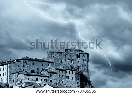 antique medieval village under stormy sky - stock photo
