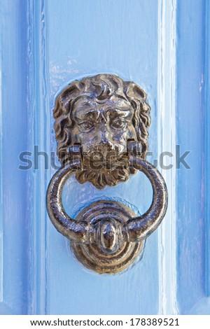Antique metal door knocker on a blue wooden door - stock photo