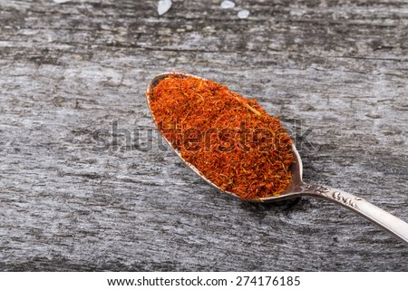 Antique metal spoon with saffron on an old wooden table. Selective focus. - stock photo