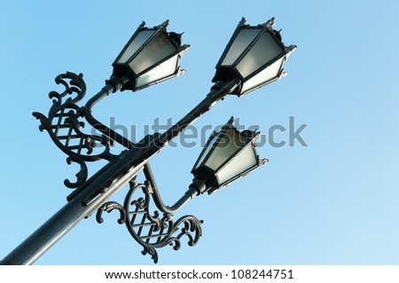 Antique metal street lamp with blue sky on background - stock photo