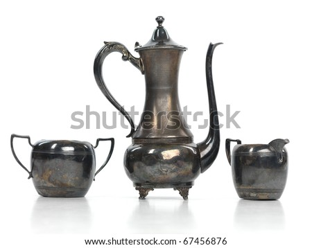 Antique metal tea pot, a milk jug and a sugar bowl isolated on white background - stock photo