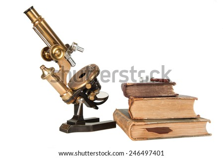 Antique microscope with closed books - stock photo