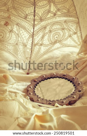 Antique mirror lying on a wedding dress with brides parasol - stock photo