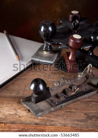 Antique morse code telegraph and stamps on vintage desk - stock photo