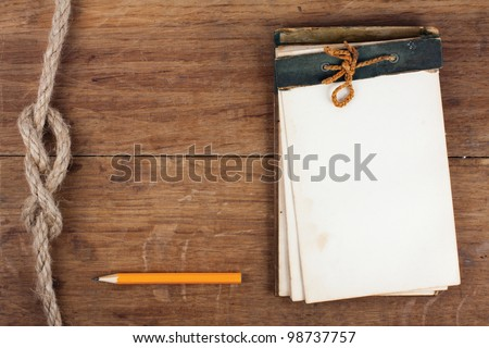 Antique notebook and pencil on wood with rope knot background