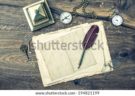 antique office supplies and writing accessories on wooden background. vintage keys, clock, glasses, feather pen, compass. retro style toned picture - stock photo
