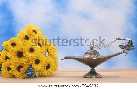 Antique Oil Lamp and Yellow Flowers on Blue and White Textured Background - stock photo