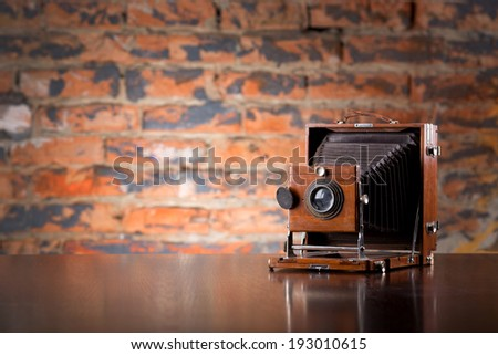 Antique Old photo Camera on wooden table - stock photo